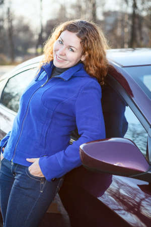 Joyful woman leaned to car smiling and looking at camera photo