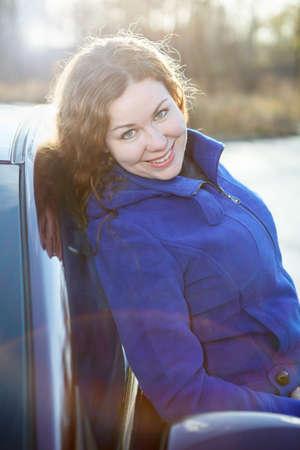 leaned: Joyful curly hair woman leaned against car in sun rays Stock Photo