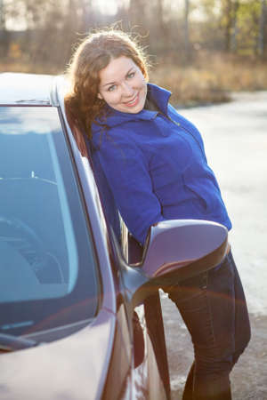 Happy curly hair woman leaned against car in sun lights photo