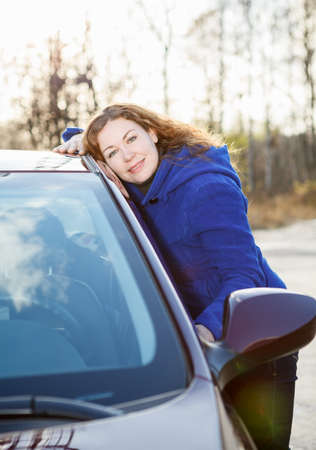 Joyful girl embracing car standing in sun lights photo