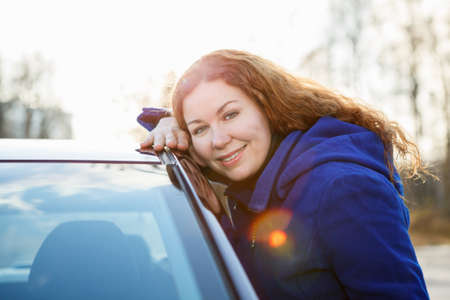 Joyful girl embracing car and looking at camera in sun lights photo