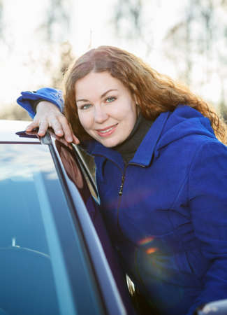 Curly girl in blue coat with car looking at camera in sun lights photo