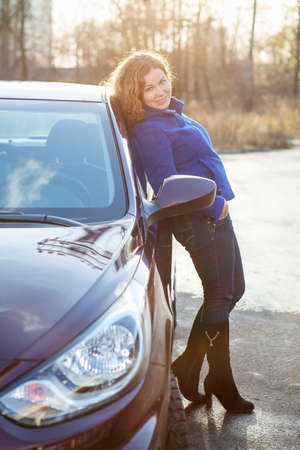 Joyful woman in full length leaned against car in sun lights photo