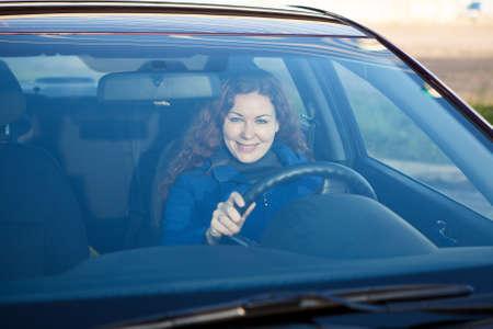 Aantrekkelijke bestuurder binnenkant van auto glimlachen door de voorruit