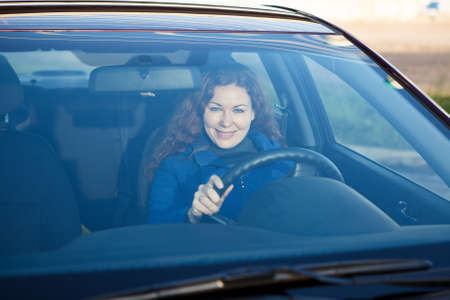 Attractive driver inside of car smiling through the windshield Stock Photo