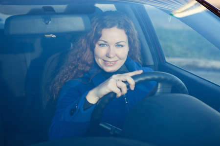 Smiling young woman the driver looking through car windglass photo
