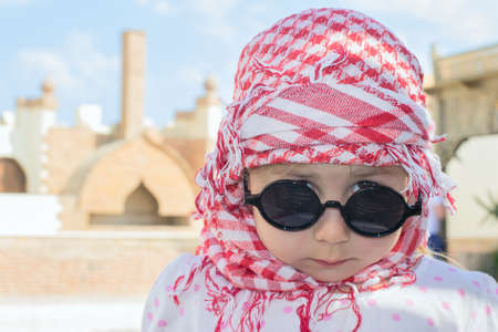 Close-up portrait of beautiful young Caucasian girl in Muslim head kerchief and sunglasses photo