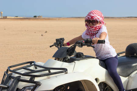 Little Caucasian girl in head kerchief and sunglasses on quadbike in desert photo