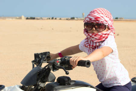 Small Caucasian child in head kerchief and sunglasses on quadbike in desert photo