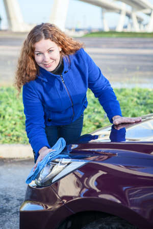 Attractive woman cleaning car headlights photo