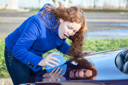 Attractive woman polishing car cowl photo