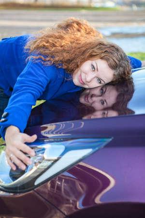 Jonge vrouwelijke bestuurder knuffelen motorkap van nieuwe auto