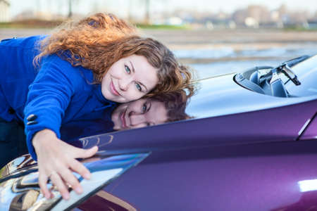 Jonge vrouwelijke chauffeur omarmen motorkap van nieuwe auto