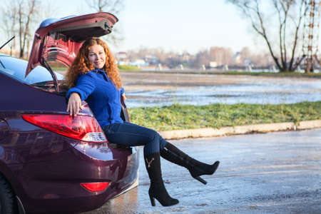 Joyous young woman sitting in car luggage trunk photo