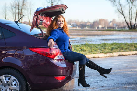 Attractive young woman sitting in car luggage trunk photo