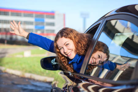 Joyous woman waving by hand from car window photo