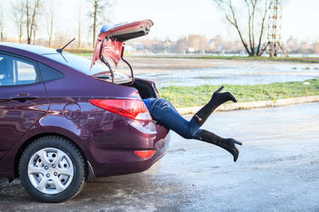Woman swinging her legs into car luggage trunk Imagens