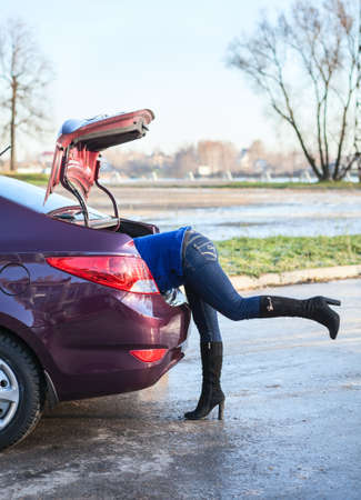 Woman body into car luggage trunk  Legs sticking out photo