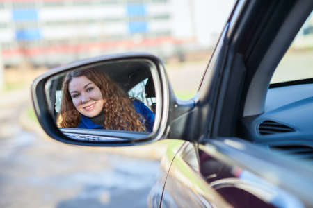 Beautiiful woman looking in car back rear-view mirror sitting in vehicle photo