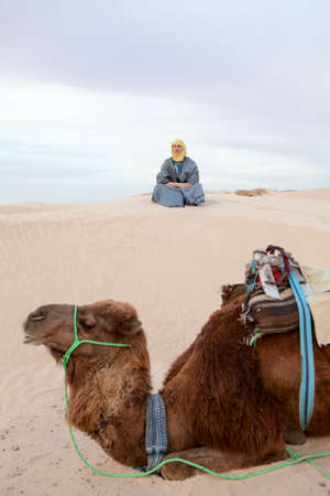 Caucasian man sitting on sand dune in desert with camel on foreground photo