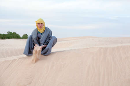 Caucasian man in protection eastern clothes pouring sand by hands on desert dune photo