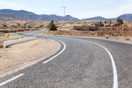 Asphalt road with white carriageway marking in mountain terrain of Africa Stock Photo - 16797647