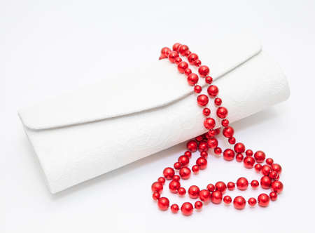 Red pearl necklace with purse on white background photo