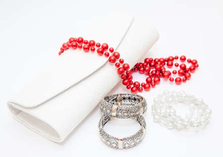 Golden braceletes red necklace with purse on white background photo