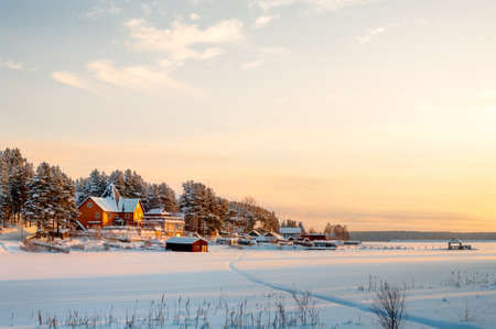 Country house on lake shore in winter sunset lights photo