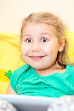 Small Caucasian girl with funny smile and wide opened eyes sitting with tablet pad Stock Photo