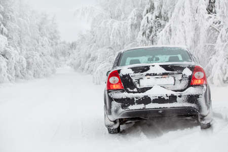 back roads: Winter white road with black vehicle standing at roadside