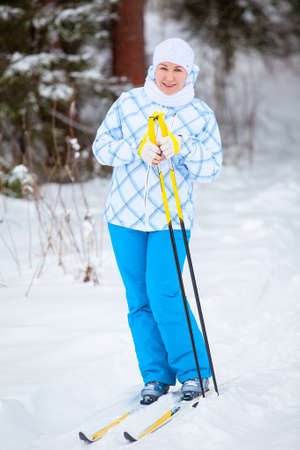 Happy young woman standing on ski with poles in hands photo