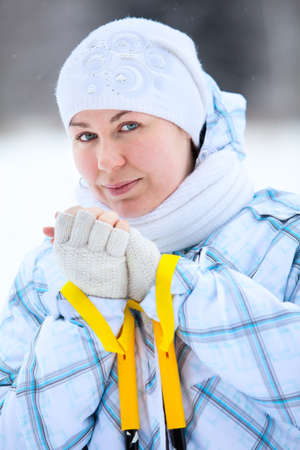 Young smiling woman warming fingers with ski poles in hands photo