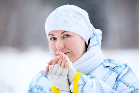 Young woman warming fingers with ski poles in hands photo