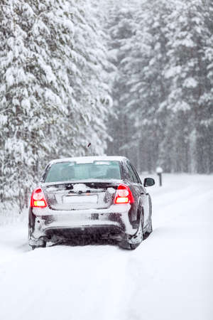 land slide: Black car standing on a country road in wintry northern forest