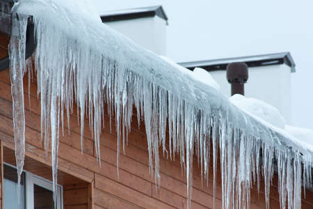 overhanging: Roof of the house with snow and icicles overhanging