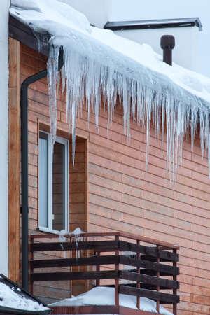 Overhangende ijspegels op het dak van het huis