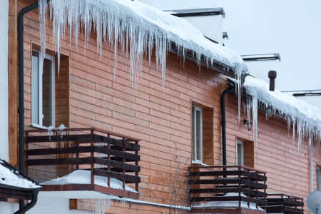 overhanging: Overhanging icicles on the house roof over balconies Stock Photo