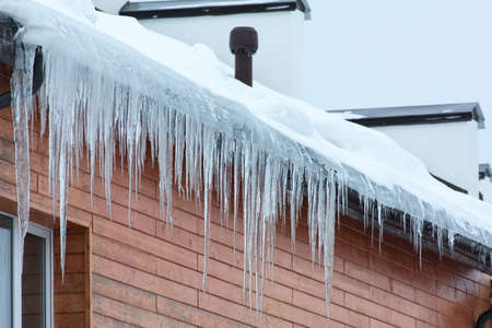 Winter hanging icicles on the house roof 免版税图像 - 18102400