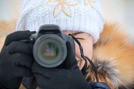 Close up female photographer with camera outdoor in winter clothes photo
