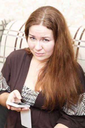Retrato de raza cauc�sica mujer infeliz joven con el tel�fono celular en la habitaci�n interior photo