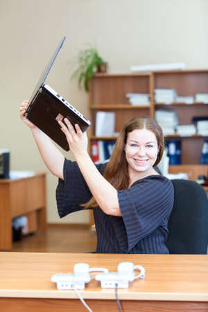 Cheerful young woman holding laptop over head while good news in office photo