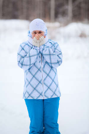 Happy Caucasian woman portrait with warming frozen hands in winter photo