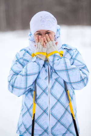 Skier Caucasian woman warming frozen hands with ski poles in winter photo