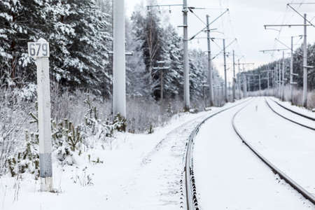 mainline: Empty electric mainline railway in winter woods with distance mark Stock Photo