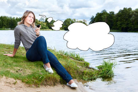Young thinking woman with mobile phone and blank thought cloud photo