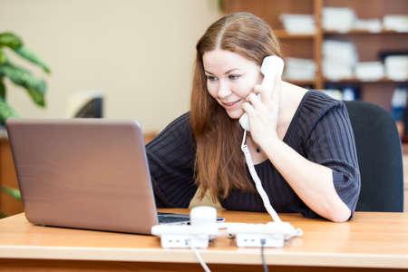 Executive aantrekkelijke zakelijke vrouw telefoneren in het kantoor
