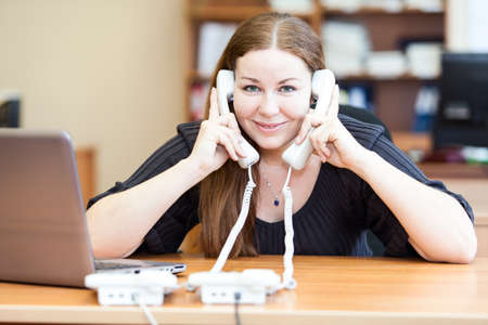 Tired executive business woman with two telephone handset calliing in office photo