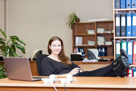 Woman resting with coffee mug on working place with legs on the table photo