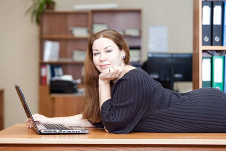 Happy joyful Caucasian woman laying on the desk with laptop in front photo
